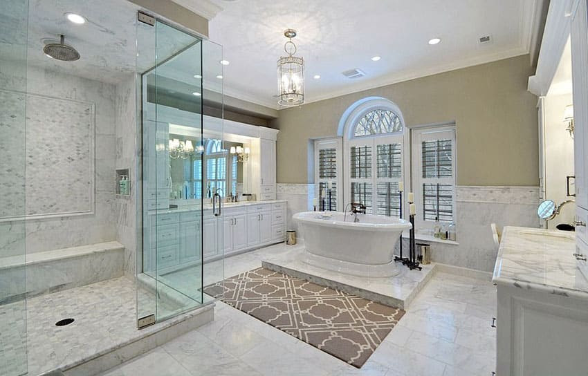 luxury master bathroom with dual side tub white vanity and marble counters floors