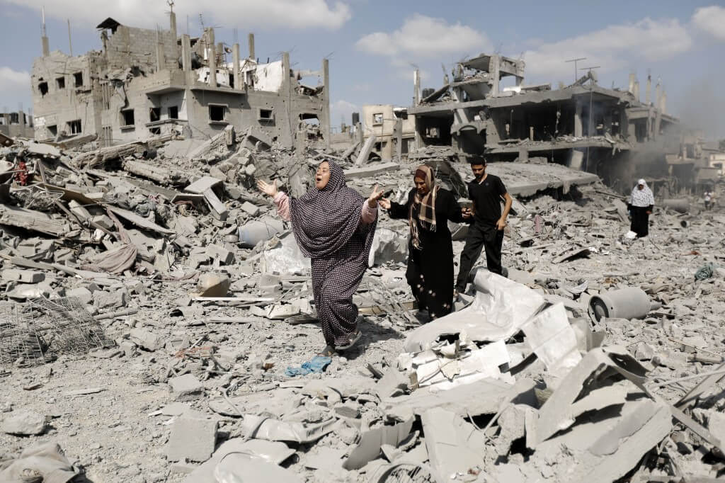 Palestinians in Gaza walk amid destroyed buildings in the northern district of Beit Hanun during an humanitarian truce on July 26, 2014. (Photo: Mohammed Abed/AFP/Getty Images)
