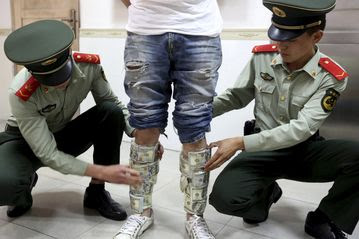 Police stop a man allegedly smuggling U.S. dollars at the border of Hong Kong and Shenzhen.