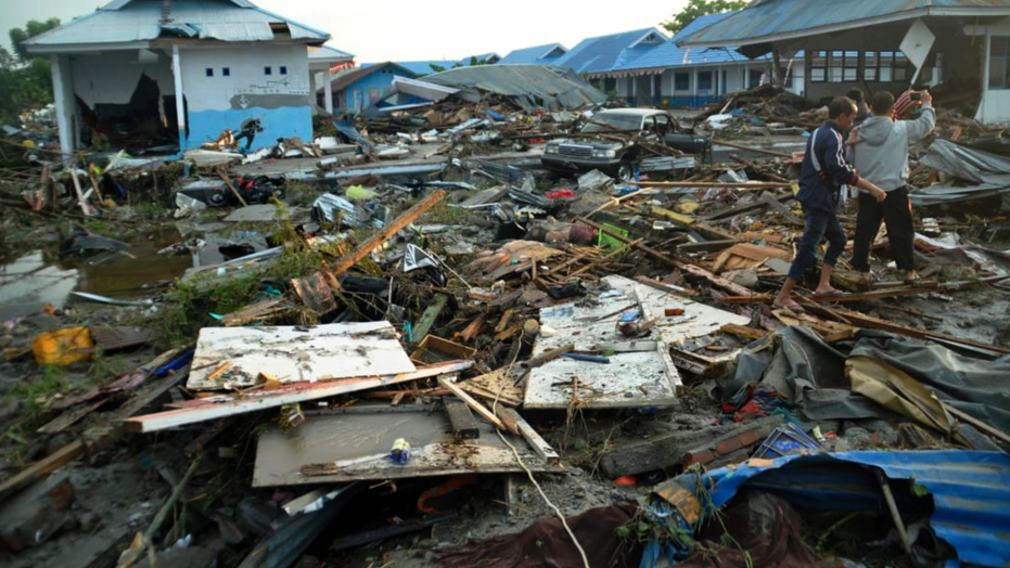 Indonesian men survey the damage following earthquakes and a tsunami in Palu, Central Sulawesi, Indonesia, Saturday, Sept. 29, 2018. A tsunami swept away buildings and killed large number of people on the Indonesian island of Sulawesi, dumping victims caught in its relentless path across a devastated landscape that rescuers were struggling to reach Saturday, hindered by damaged roads and broken communications. (AP Photo/Rifki)