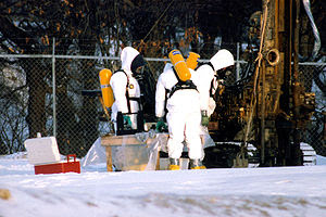 Workers in hazmat suits check the status of a ...