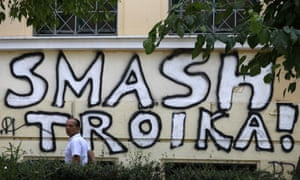 A pedestrian passes graffiti referring to the officials from the European Union, European Central Bank and International Monetary Fund, together known as the troika, in Athens.