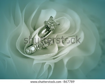 stock photo Soft blue vignette image of wedding rings in the folds of the