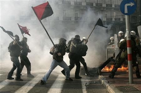 Self-styled anarchists armed with wooden sticks fight against the police in an attempt to release a detained comrade (on the floor) in a cloud of tear gas outside the Greek Parliament in Athens in this February 22, 2007 file photo. REUTERS-Yannis Behrakis-Files