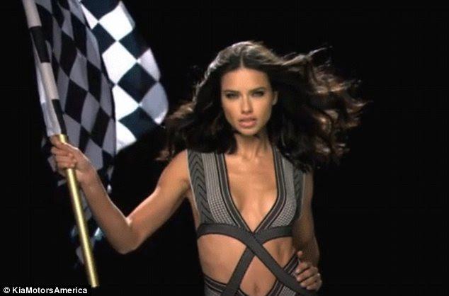 Voando a bandeira: Adriana Lima é impressionante em um carro Kia comercial para ser exibido durante o Super Bowl