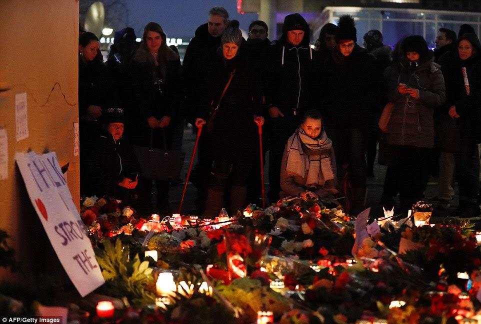 Vigília: Um mar de velas e flores cobrem o pavimento perto de onde o ataque terrorista aconteceu 24 horas atrás