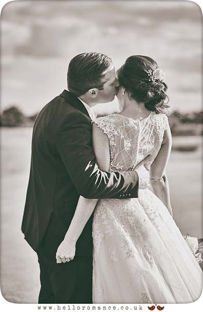 Cute moment when groom kisses bride, candid black and white wedding photo - www.helloromance.co.uk