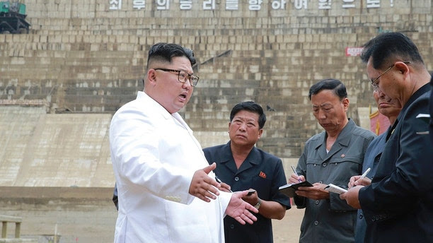 """In this undated photo provided on Tuesday, July 17, 2018, by the North Korean government, North Korean leader Kim Jong Un, left, inspects the construction site of a hydroelectric power plant in North Hamgyong Province, North Korea. State media say that Kim has harshly reprimanded local officials over a delayed construction project. The slogan in the background reads: &qu   ot;March toward the final victory!"""" Independent journalists were not given access to cover the event depicted in this image distributed by the North Korean government. The content of this image is as provided and cannot be independently verified. Korean language watermark on image as provided by source reads: """"KCNA"""" which is the abbreviation for Korean Central News Agency. (Korean Central News Agency/Korea News Service via AP)"""