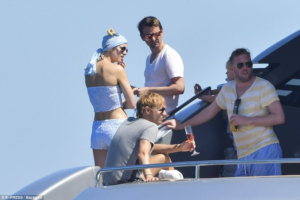 Close bond: The statuesque blonde and her rocker boyfriend were seen chatted in the shade with a group of friends