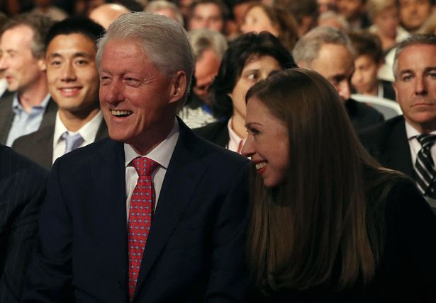 Former U.S. president Bill Clinton (L) and his daughter Chelsea Clinton (R) look on