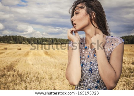Young sensual & beauty woman in a fashionable white-blue dress pose on field.