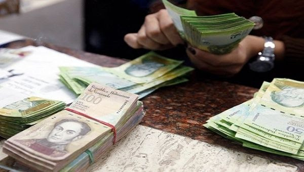 A cashier counts bolivars at a money exchange in Caracas, Venezuela.