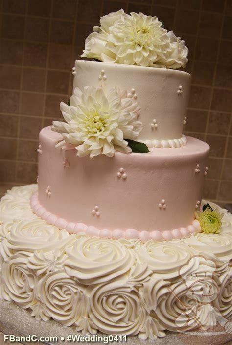 Buttercream rose swirls on the bottom tier of this wedding