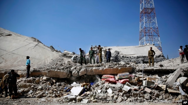 FILE - Policemen gather at the site of a Saudi-led airstrike on the police headquarters in Sana'a, Yemen, Jan. 18, 2016.