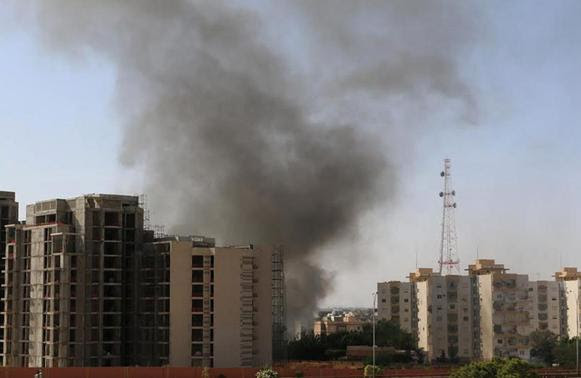 Smoke rises near buildings after heavy fighting between rival militias broke out near the airport in Tripoli July 13, 2014.   REUTERS- Hani Amara
