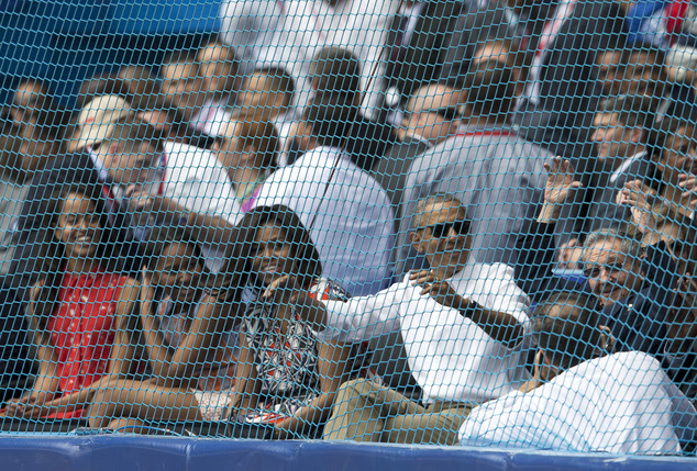 Cuban President Raul Castro, right, cheers next to U.S. President Barack Obama, his wife Michelle, and their daughters Sasha and Malia, at the start of a bas...