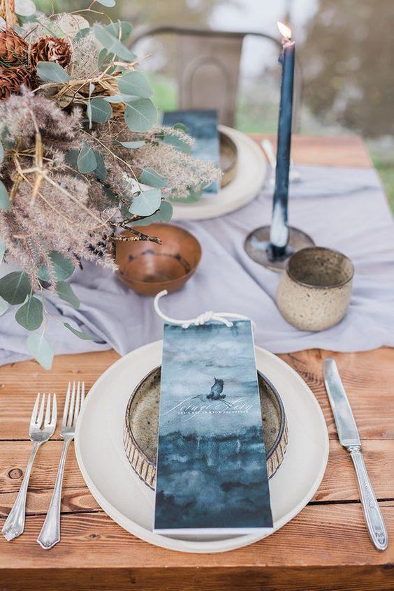 eine Hochzeit tablescape mit indigo Platzkarten, Kerzen und eine hellblaue Tischläufer