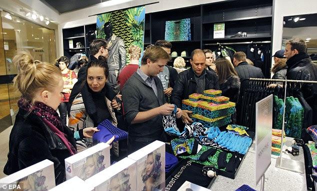 Compradores carregar suas armas com peças da coleção.  Direita, um homem compra inúmeras caixas contendo jóias, calçados e acessórios