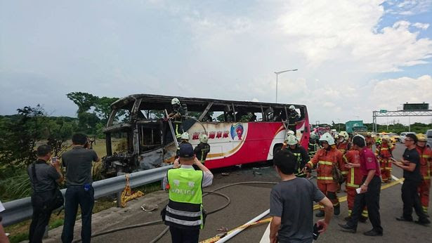 Police and firemen inspect the scene of the coach fire
