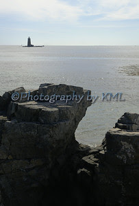 lighthouse beyond the rock formation