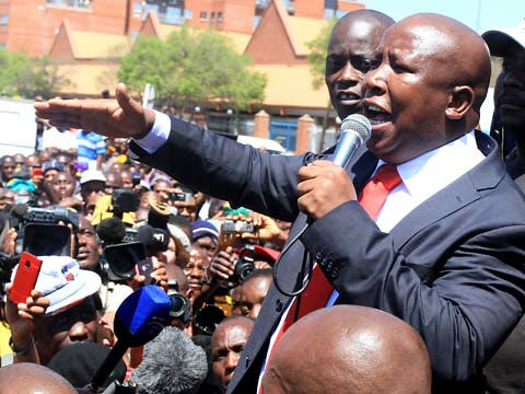 Julius Malema, expelled ANC Youth League president, speaks to supporters outside court at Polokwane where he was indicted on one charge of money laundering. Malema says the charge is politically motivated. by Pan-African News Wire File Photos