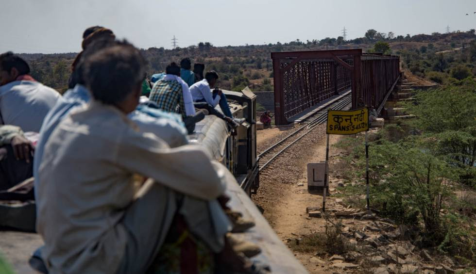 Un tren con el techo repleto de viajeros cruza el puente sobre el río Kuno, entre Gwalior a Sheopur, India.