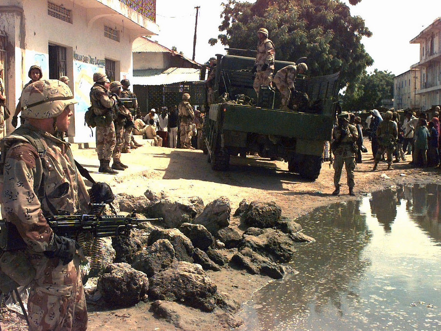 U.S. Marines load ammunition and weapons seized in a raid on Mogadishu, Somalia's, Bakara Market December 2006. A Marine stands holding a M60 machine gun, left, pointing it at a crowd of Somali civilians standing at the right. (Photo/Expert Infantry via Flickr)