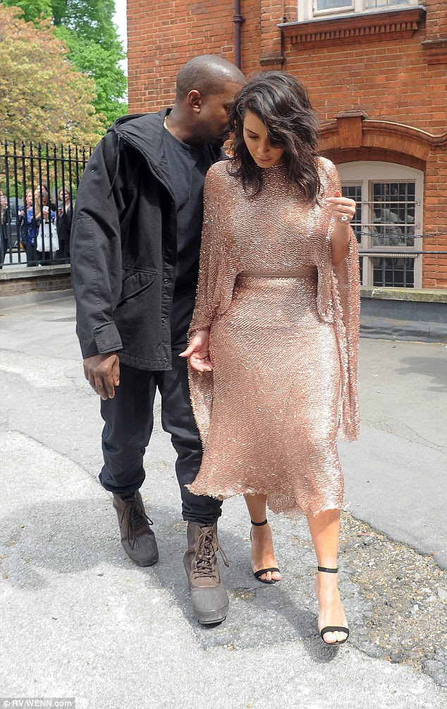 Intimate moment: Kanye was seen whispering in his wife's ear as the pair made their way into the venue