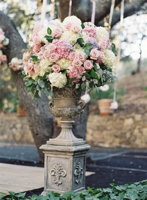 Stone urn wedding flower arrangement with rose and