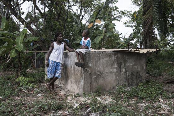 Ted y su hijo sentados sobre su cisterna, que no recoge agua de lluvia desde hace meses.