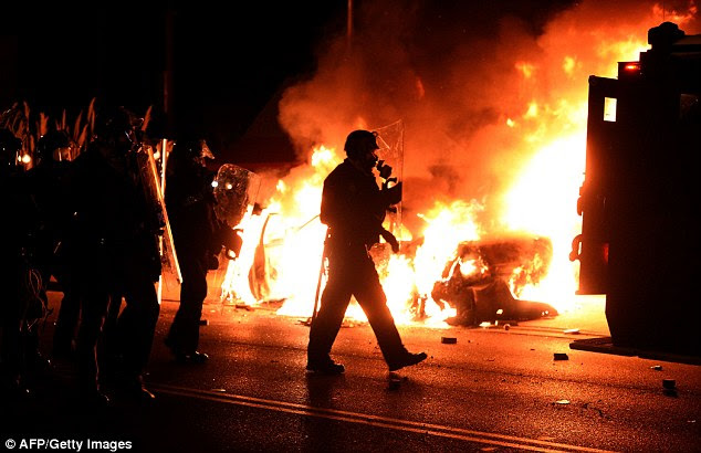 ON DEAF EARS:A police officer walks by a burning squad car during riots on Monday night