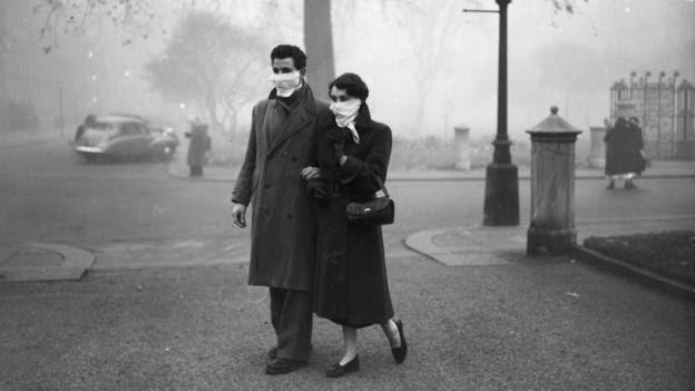 A couple walks the streets of London in November 1953 (Credit: Credit: Monty Fresco/Topical Press Agency/Getty Images)