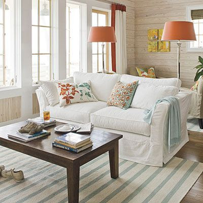 Choose a Sunny Palette    Crisp whites combined with punches of bright colors immediately transport you to the coast. In this living room, aqua accents in the pillows, throw, and rug mimic the ocean's dazzling blues, and the pops of bright orange are inspired by the magnificent hues of the setting sun. Whitewashed horizontal shiplap planking evokes the feel of old Gulf-front beach houses.