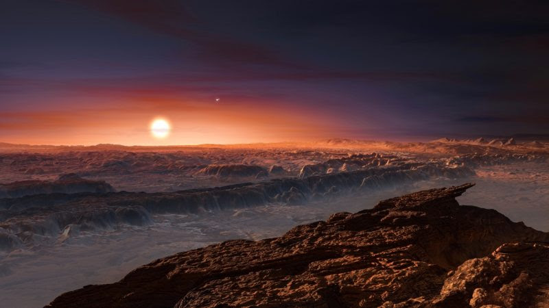 View larger. | This artist's impression shows a view of the surface of the planet Proxima b orbiting the red dwarf star Proxima Centauri, the closest star to the Solar System. The double star Alpha Centauri AB also appears in the image to the upper-right of Proxima itself. Proxima b is a little more massive than the Earth and orbits in the habitable zone around Proxima Centauri, where the temperature is suitable for liquid water to exist on its surface.