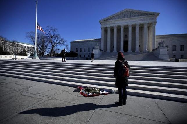 Flowers are seen as a woman stands in front of the Supreme Court building in Washington D.C. after the death of U.S. Supreme Court Justice Antonin Scalia, February 14, 2016. REUTERS/Carlos Barria