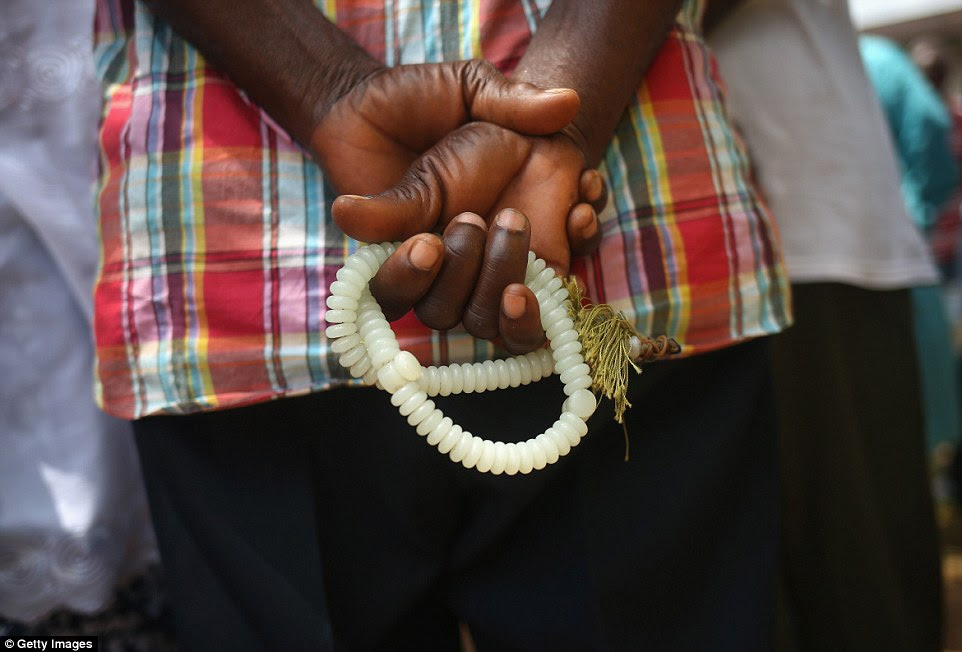 Turning to religion: A Muslim man holds his prayer beads as an Ebola burial team arrives to collect the body of a neighbor on Saturday