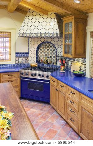 A Spanish style kitchen with blue counter tops and ceramic tile