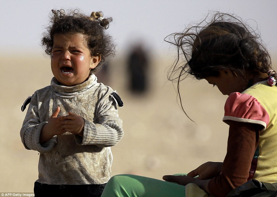 A refugee toddler cries as she and another child head towards the Syrian border after fleeing the battle for Mosul