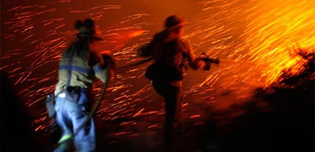 Bomberos trabajan para detener el fuego. | Reuters
