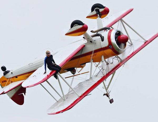 Wing walker sentado na asa durante a apresentação. (Foto: Thanh V Tran/AP Photo)