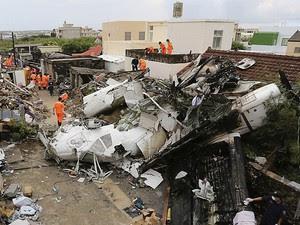 24/7 - Equipe de resgate trabalha em meio aos destroços do avião da TransAsia Airways e das casas que ele atingiu em Penghu, Taiwan (Foto: Reuters/Stringer)
