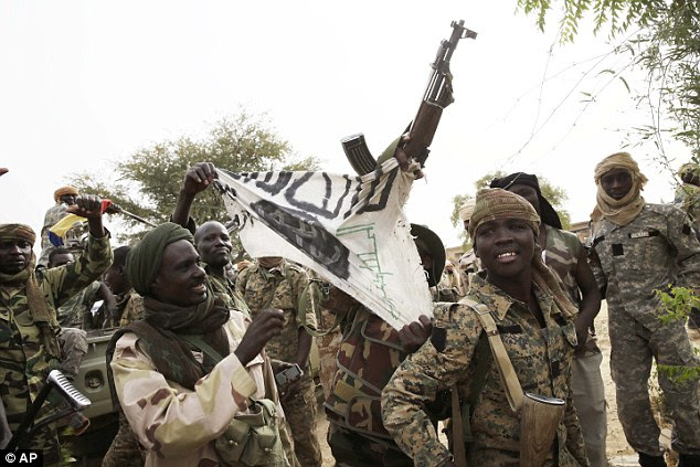 Defence: Officials believe they were taken so they could be used as human shields when troops arrived. Pictured: Chadian army celebrates entering Damasak - showing off one of Boko Haram's flags