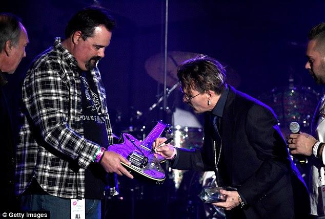 Boa causa: Johnny autografou um de seus assinatura guitarras Duesenberg Series Alliance, que foi então leiloados em prol da organização sem fins lucrativos beijo de Rhonda que ajuda as pessoas com câncer