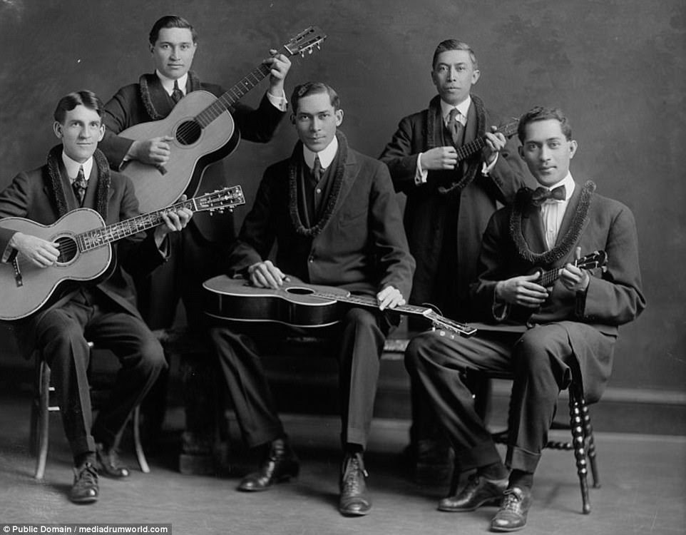 A Hawaiian quintet - all suited and holding guitars and ukuleles - pose for a photograph in Aloha in a picture taken in 1905