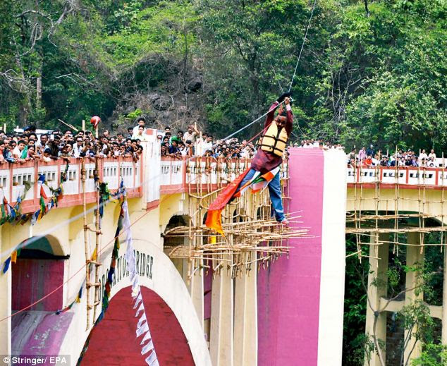Tragic: Stuntman Sailendra Nath Roy, pictured on the slide before he died, suffered a heart attack after getting stuck part-way through his feat