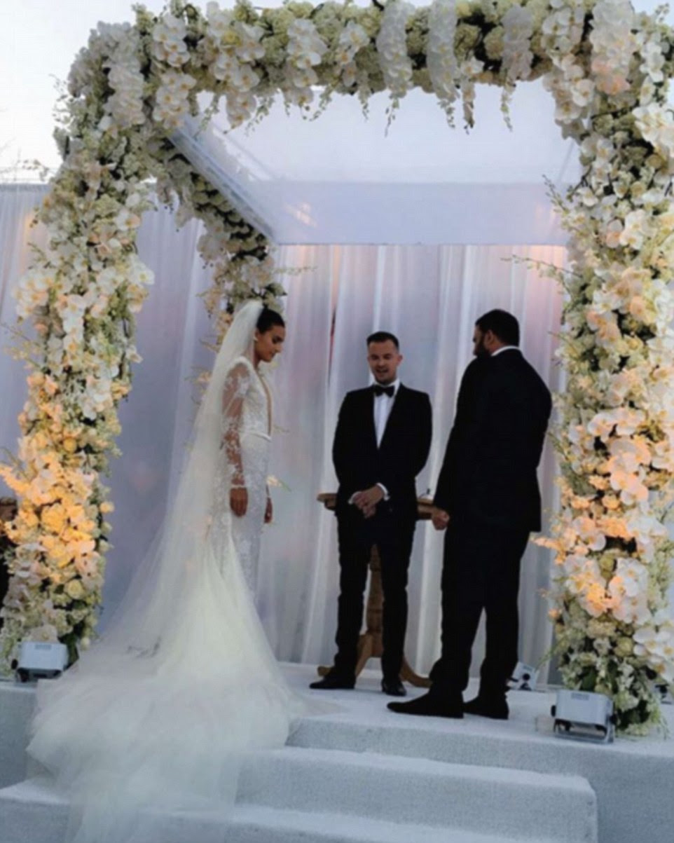 The couple exchanged their vows under a white floral archway at Wynwood Walls outdoor mural park in Miami