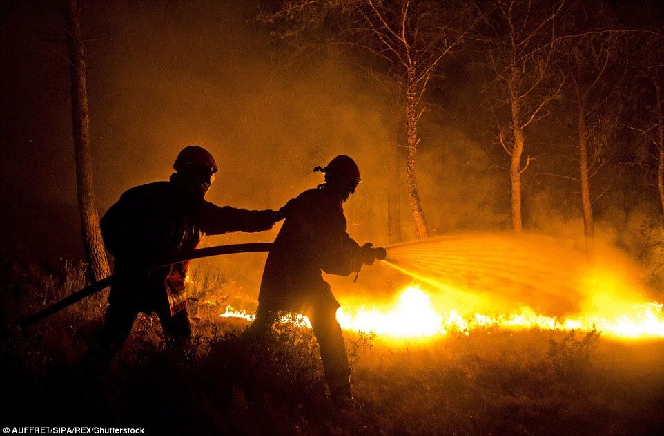 Como a escuridão caiu ontem à noite os bombeiros continuaram a mangueira para baixo áreas de floresta em um esforço para evitar que o fogo se espalhando