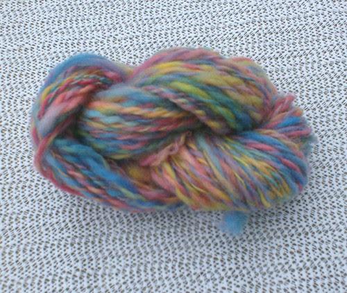 Skein of blue red yellow pink green purple handspun wool yarn