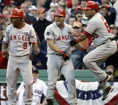 Los Angeles Angels' Bobby Abreu, right, celebrates with teammates Chone Figgins (9) and Kendry Morales, center, after scoring in the 9th inning against the Boston Red Sox during Game 3 of an American League baseball division series in Boston, on Sunday, Oct. 11, 2009.  The Angels won, 7-6.