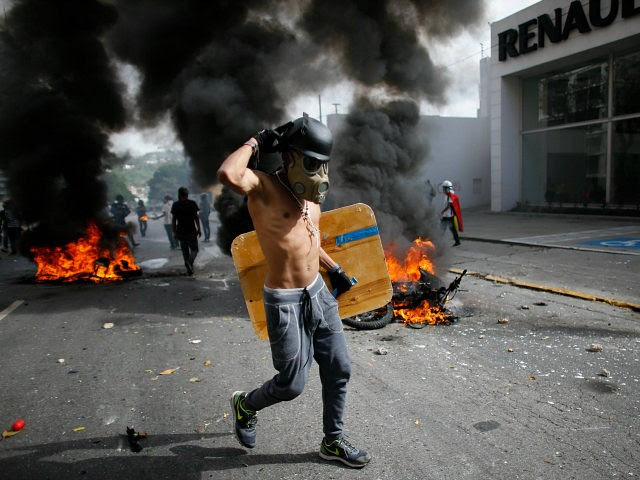 An anti-government demonstrator walks past two National Guard soldiers' motorcycles that were set on fire by protesters when the soldiers ran from their bikes after falling during clashes with protesters in Caracas, Venezuela, Wednesday, May 31, 2017. Protesters have flooded the streets of Venezuela for months, demanding new elections and faulting President Nicolas Maduro's leadership for the country's triple-digit inflation, surging crime rates, and dire shortages of food and medicine. (AP Photo/Ariana Cubillos)